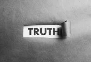 Torn paper with truth word behind it, black and white photo